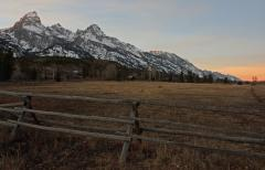 The last light of the day falls on the Tetons above a ranch nort